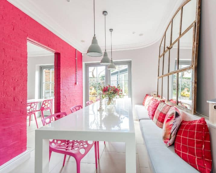 This small dining room has an eye-catching bubblegum pink stone wall that pairs well with the modern plastic pink chairs of the long white modern dining table. On the other side of this is a built-in long bench with light gray cushions and red pillows.