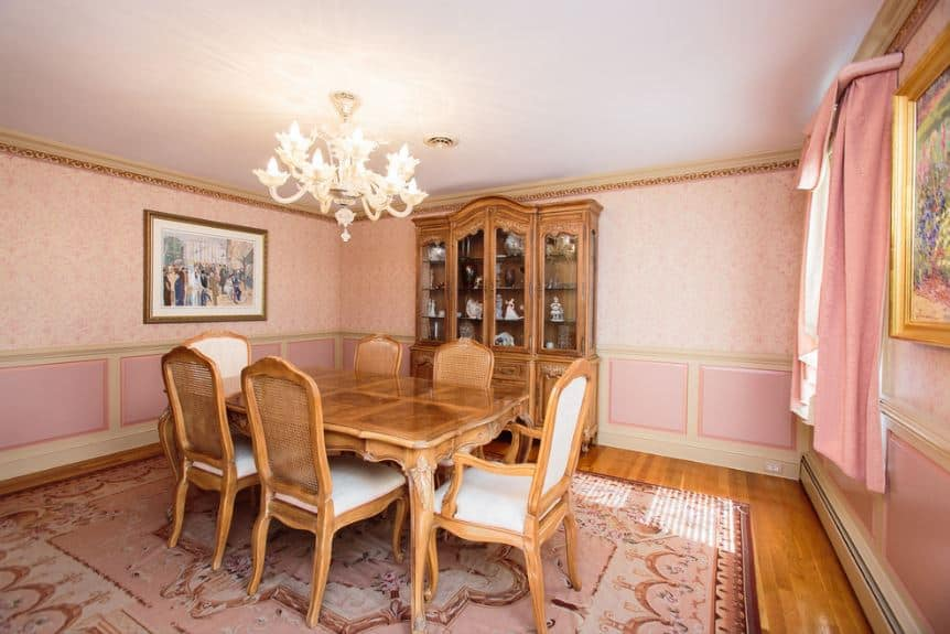 This is a dining room with a nice fusion of traditional elements with a chic quality. The wooden dining set matches with the dining room cabinet. This has a nice chic background of pink patterned wallpaper and pink curtains.