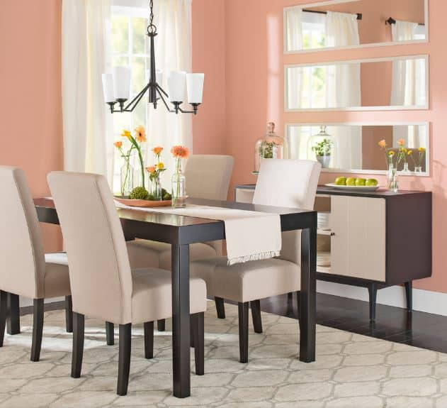 This simple dining room has a small modern chandelier hanging over the black wooden dining table with a light table runner that matches the light gray cushions of the wooden chairs as well as the patterned area rug over the dark hardwood flooring.