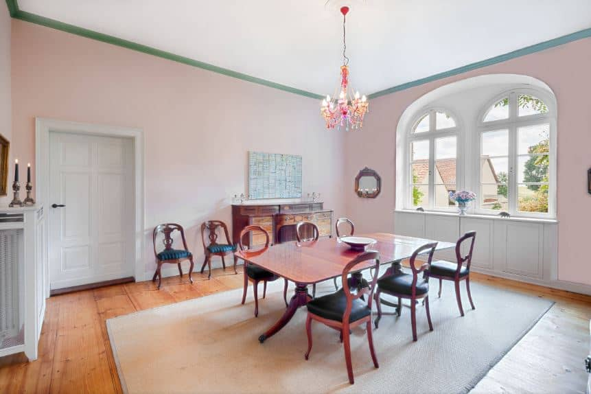 The tall pink walls have a contrasting green molding by the white ceiling. These walls and ceiling are brightened by the abundant natural lighting coming from the arched windows by the head of the wooden rectangular dining table.