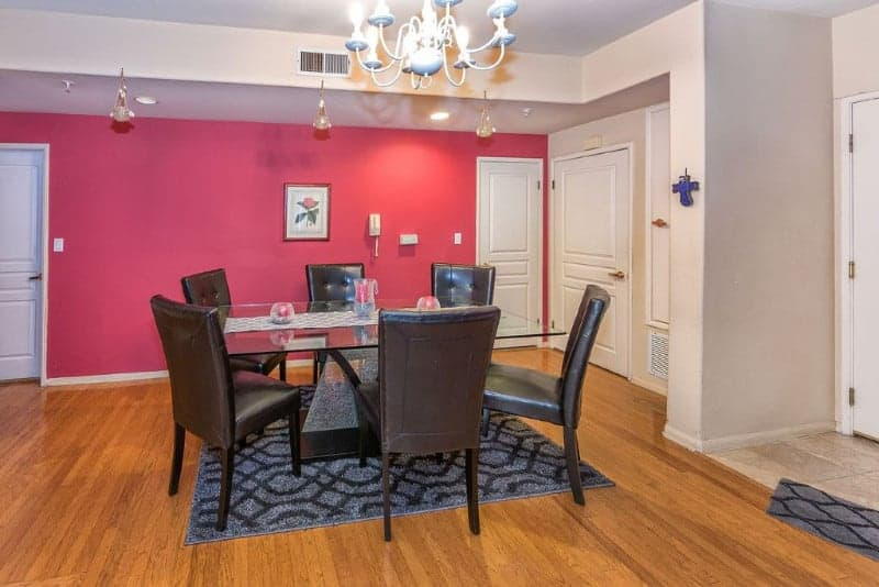 The walls of this simple dining room has two tones. One is beige that goes well with the white doors and white chandelier. The other is pink that provides a lovely colorful background for the glass-top dining table and the black leather cushioned chairs.