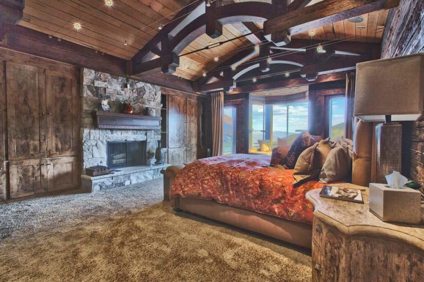 Large rustic primary bedroom featuring a stunning wooden ceiling with large beams along with carpeted flooring. The room offers rustic furniture along with a large fireplace.