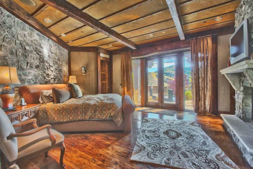 Large rustic primary bedroom with a stone wall, hardwood flooring and a rustic ceiling. The room has a large cozy bed lighted by two table lamps and a large stone fireplace.