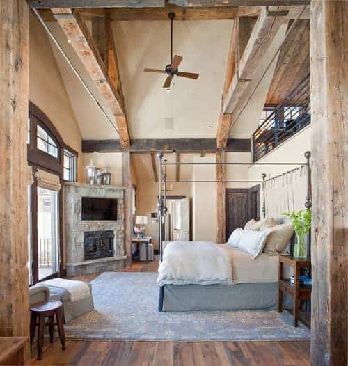 Rustic primary bedroom featuring a tall ceiling with large rustic beams. The room also features hardwood flooring topped by a large gray rug along with a fireplace with a widescreen TV on top.