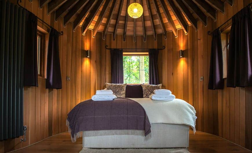 A stunning primary bedroom with rustic walls and ceiling with amazing beams lighted by warm lighting. The room has a gorgeous bed setup.