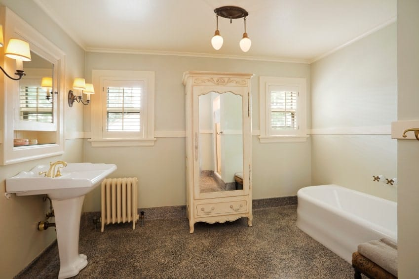 There is a tall and narrow beige cabinet with a mirror on its front standing out against the light green walls accented with a white tub on one side and a white pedestal sink on the other paired with a white-framed mirror flanked with wall-lamps.
