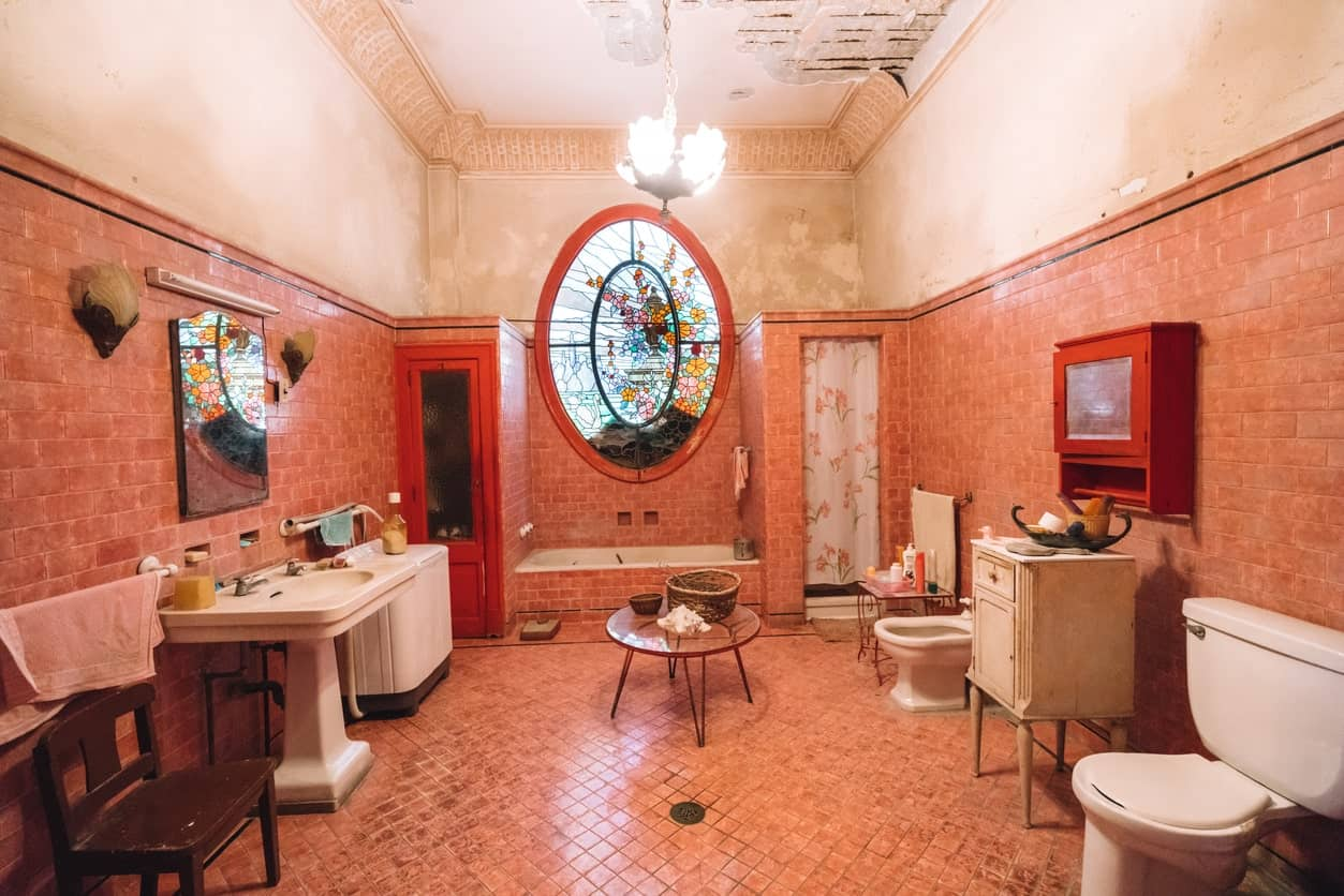 The centerpiece of this large bathroom is the large stained glass oval window above the bathtub that is flanked by two enclosed areas. one has a shower curtain while the other has a wooden door with glass in the middle. All of these are given a nice background of brick-colored tiles.