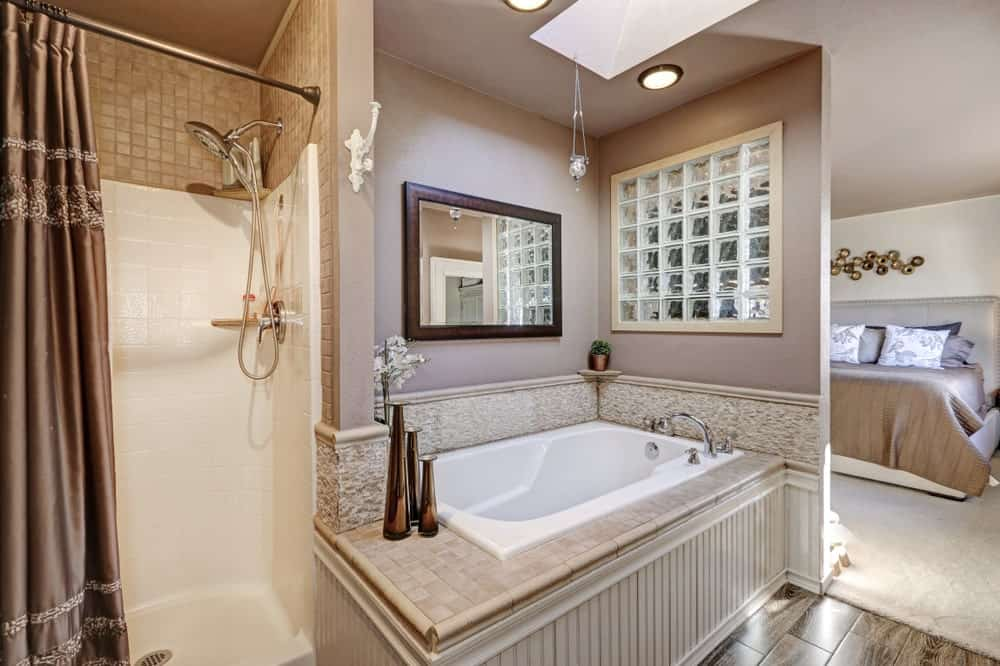This lovely bathroom is open to the bedroom separated with a half wall with a gray hue that matches the ceiling that forms an alcove for the small bathtub housed in beige tiles matching with those above the white walls of the shower area.