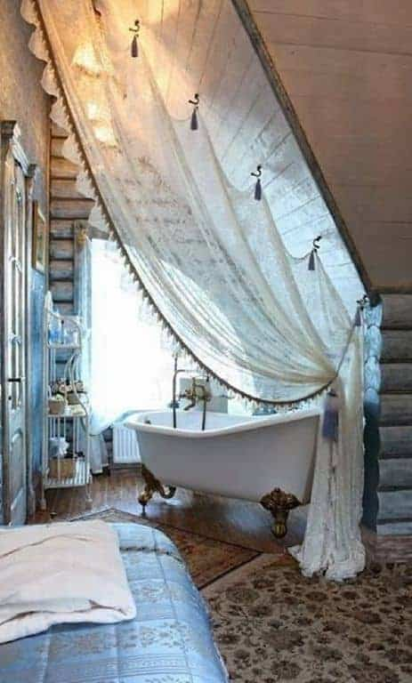 The white freestanding tub with intricate brass legs is placed in a charming curtained alcove of tall shed wooden ceiling, arched window and a hardwood flooring that is topped with a patterned area rug to protect the floor from water.
