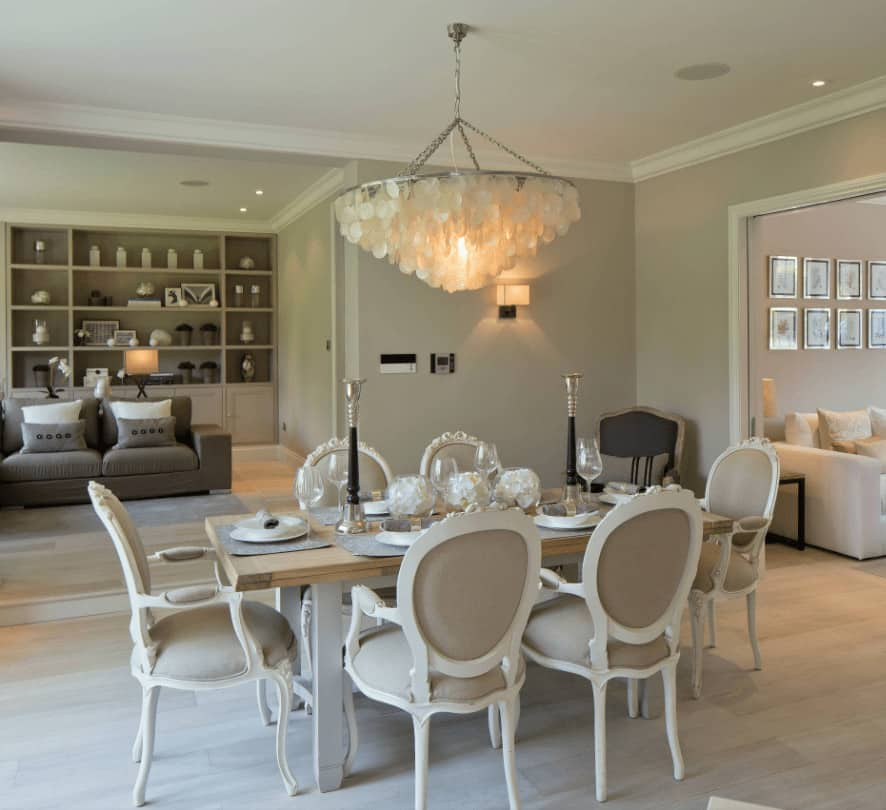 An open dining area illuminated by a shell chandelier that hung over the wooden dining table topped with tall candle holders. It is surrounded by classy beige chairs that sit on light wood plank flooring.