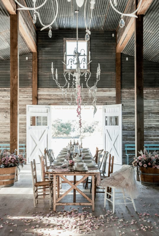 This dining room is framed with wooden columns attached to the light hardwood flooring and ripple iron ceiling with hanging white chandeliers. It has a rustic dining set and a double door that opens to the yard.