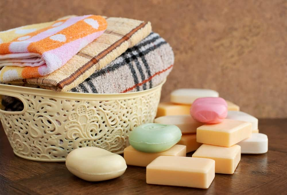 A basket of folded bath towels surrounded by various soaps on wooden desk.