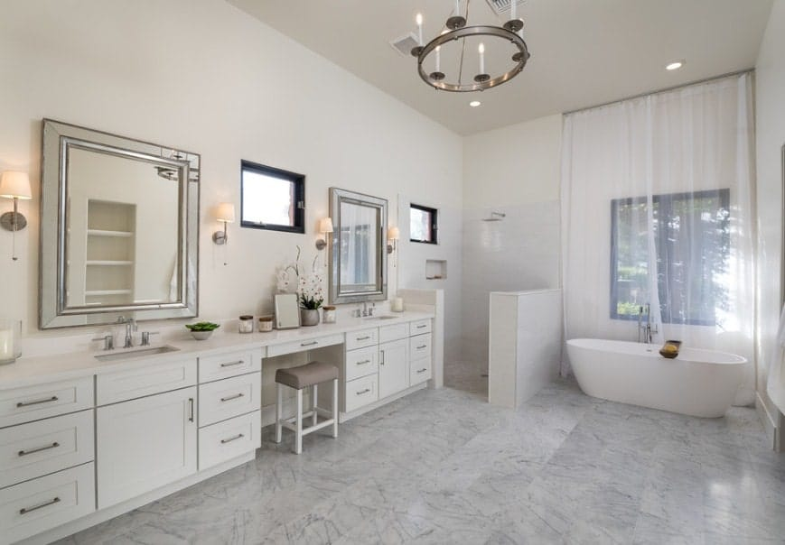 White master bathroom with gray tiles flooring and a tall ceiling. The room offers a walk-in shower and a freestanding tub.
