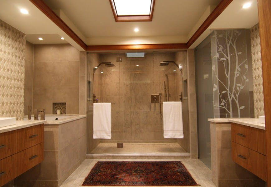 Large and elegant master bathroom featuring two sink counters, a walk-in shower room with two shower heads and a corner deep soaking tub. The room is lighted by a skylight.