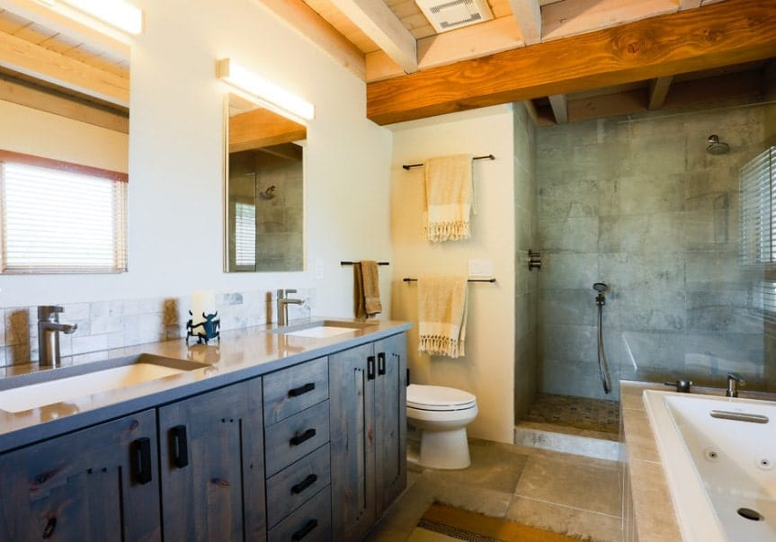 A southwestern style master bathroom with a walk-in shower, a deep soaking tub and a sink counter with two sinks.