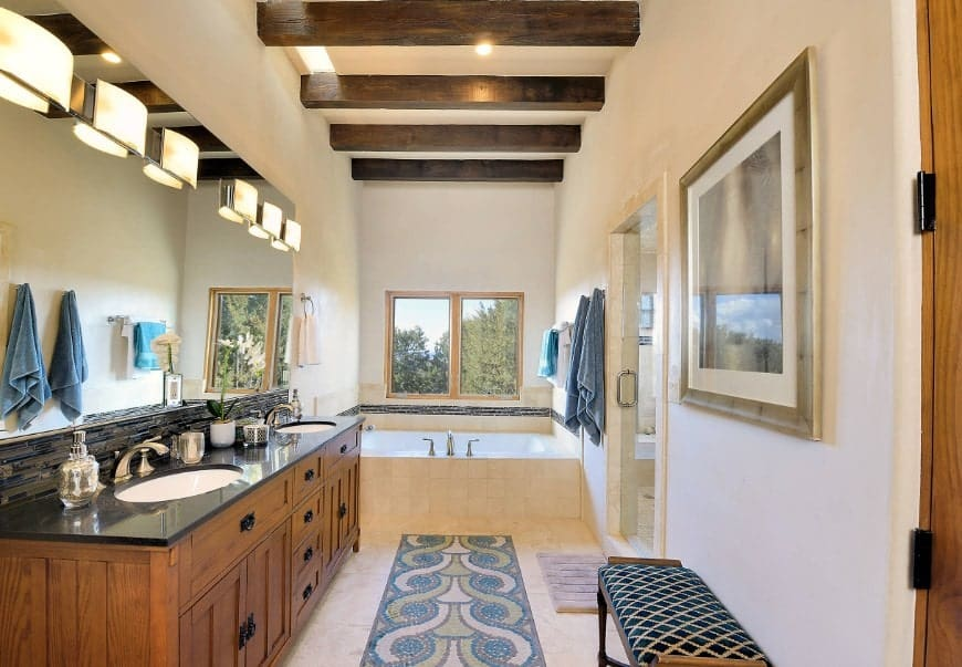 This southwestern style master bathroom offers a single sink counter with two sinks lighted by classy wall lights. The ceiling features exposed beams. There's a walk-in shower room and a deep soaking tub near the window.