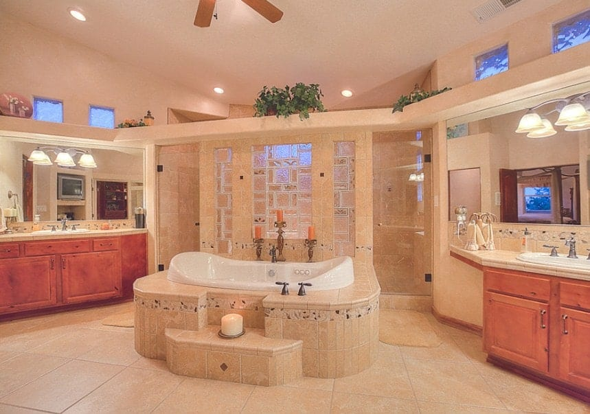 Large southwestern style master bathroom with two sink counters lighted by classy wall lights along with a drop-in tub in the center and a walk-in shower room.
