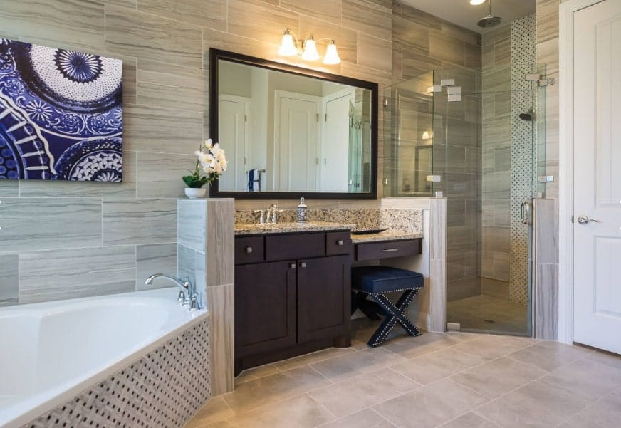 This southwestern style master bathroom offers a corner bathtub and a corner walk-in shower along with a powder area and a single sink counter.