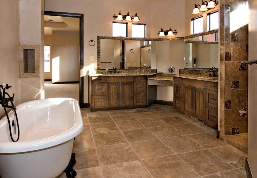 A spacious master bathroom featuring rustic sink counters lighted by gorgeous wall lights along with a freestanding tub and a walk-in shower room.