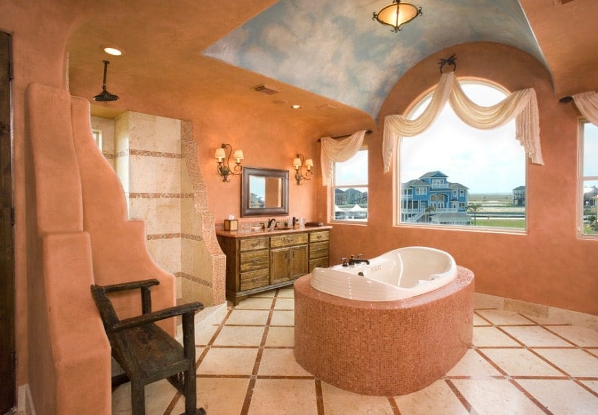 Orange master bathroom with an arch ceiling decorated with the sky. There's a drop-in tub on the center along with an open shower.