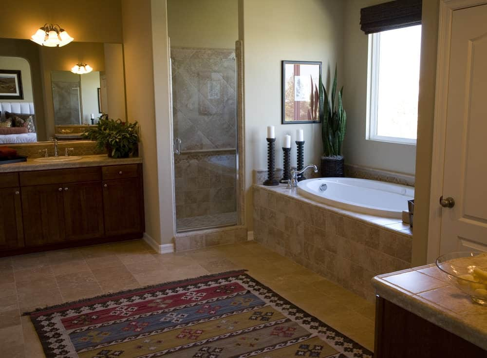 This primary bathroom offers a walk-in corner shower, a deep soaking tub near the window and a sink counter lighted by classy wall sconces.