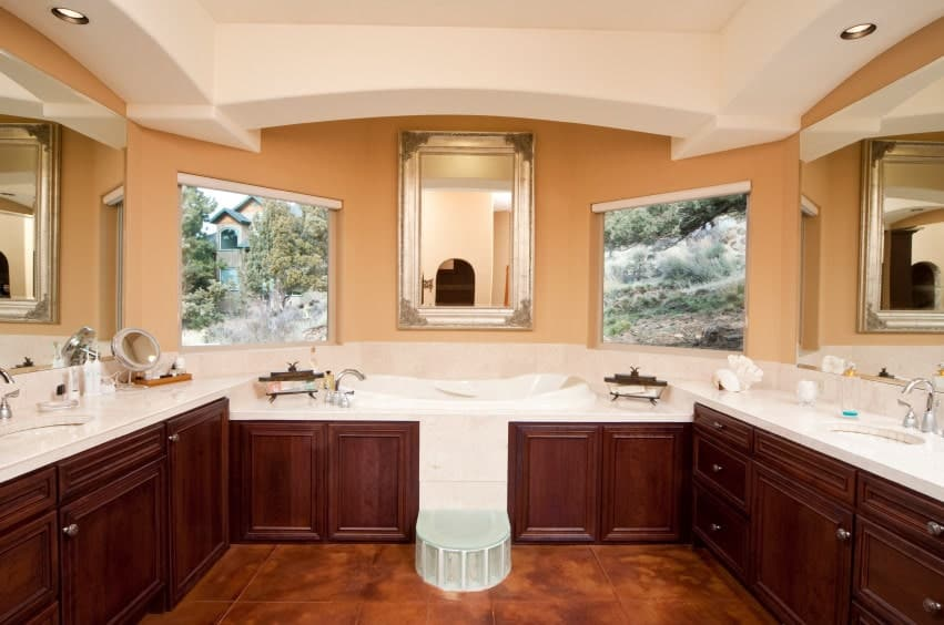 This primary bathroom features brown cabinetry and two sink counters, along with a gorgeous deep soaking tub and a tray ceiling.