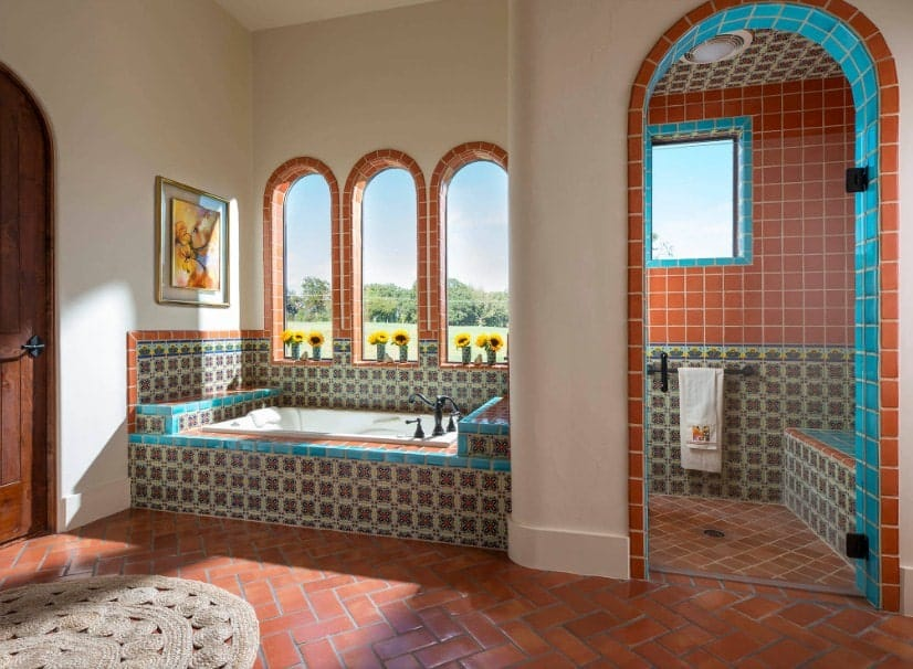 A southwestern style primary bathroom with a deep soaking tub and a walk-in shower room both featuring the same classy design.
