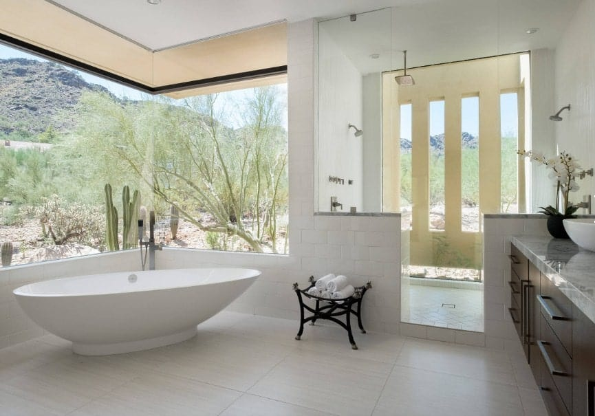 This primary bathroom features white tiles flooring and glass windows overlooking the stunning outdoor view. There's a freestanding tub and an open shower room.
