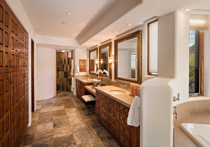A long primary bathroom with stylish cabinetry and flooring. It offers a corner tub near the windows, a powder area in between two sinks along with a corner shower.
