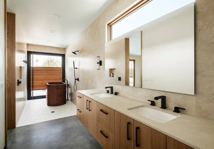 A bright southwestern style primary bathroom with a soaking tub near the open shower along with a floating vanity with two sinks.