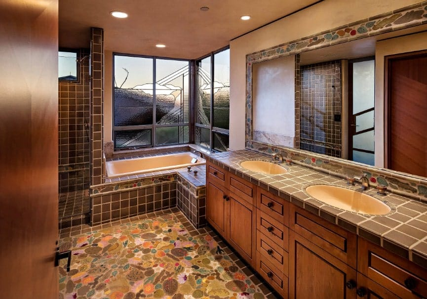 This primary bathroom features classy tiles flooring. It also features a double sink, a walk-in corner shower and a deep soaking tub near the windows.