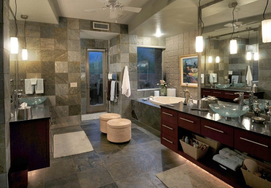 Large southwestern primary bathroom with stylish tiles flooring and walls. It also features stunning glass vessel sinks on gorgeous sink counters along with a drop-in tub and a walk-in shower.