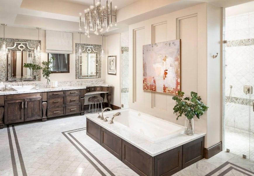 A large and bright primary bathroom with rustic cabinetry and a tray ceiling. The room offers a deep soaking tub lighted by a fancy ceiling light.