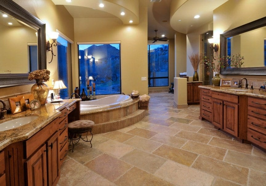 A spacious southwestern master bathroom with two sink counters and a drop-in tub near the glass windows with relaxing outdoor views.