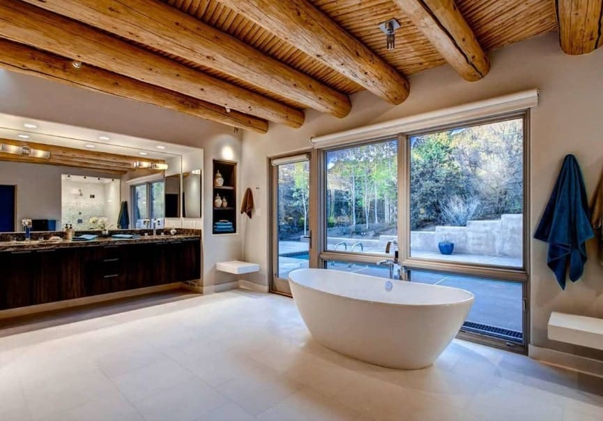 Large primary bathroom featuring tiles flooring and a wooden ceiling with logs beams. The room offers a freestanding tub and a doorway leading to the outdoor swimming pool area.