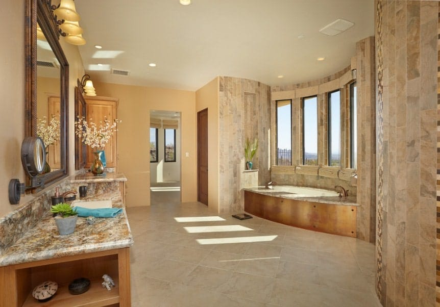 Large primary bathroom with a deep soaking tub near the windows along with classy sink counter slighted by gorgeous wall lights.