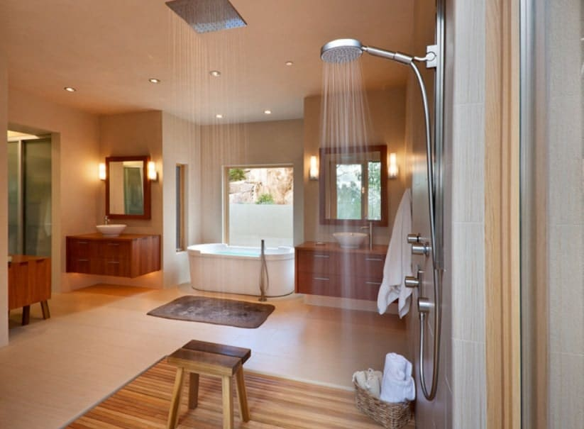 This large primary bathroom offers an open shower with a shower head and a rain shower. There's a freestanding tub and a couple of vessel sinks as well.