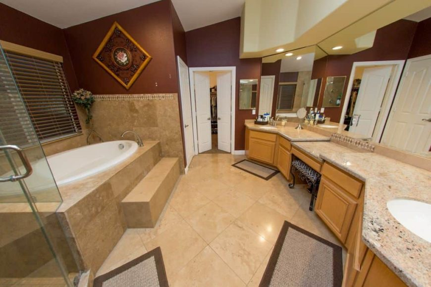 A beautiful master bathroom with classy tiles flooring along with stunning walls and ceiling. The room offers a powder area, two sinks, a drop-in tub and a walk-in shower room.