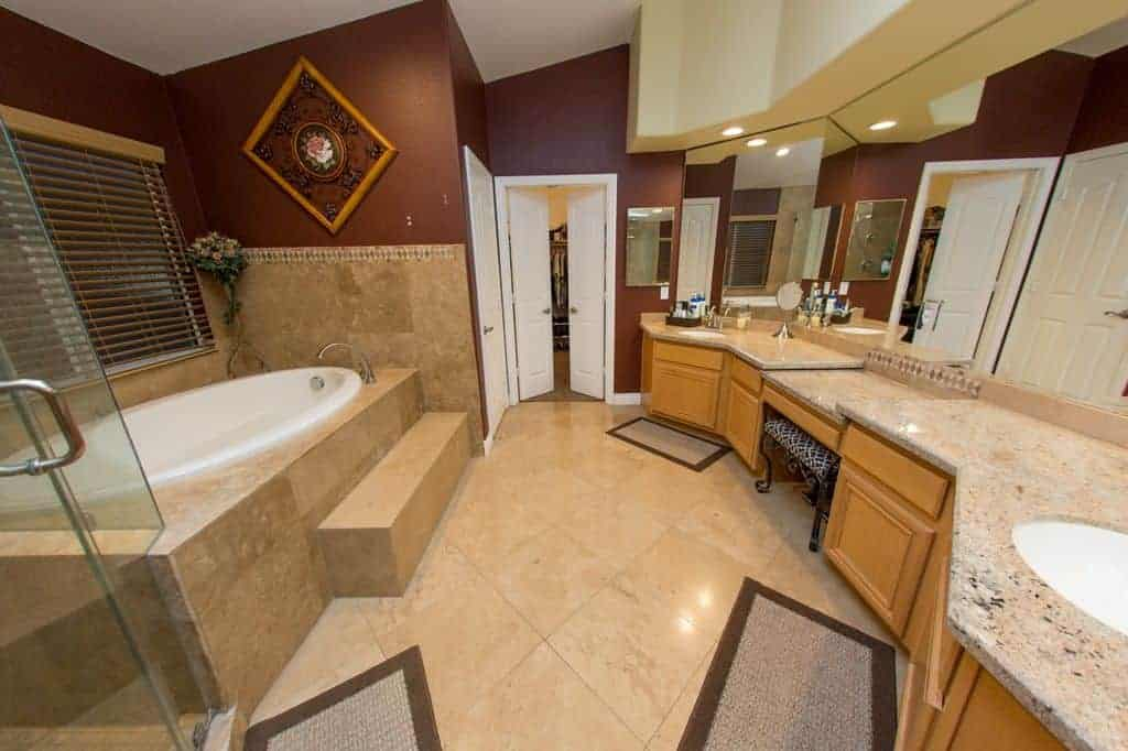 A beautiful primary bathroom with classy tiles flooring along with stunning walls and ceiling. The room offers a powder area, two sinks, a drop-in tub and a walk-in shower room.