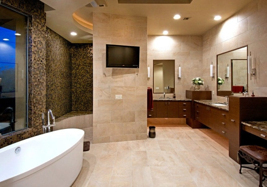 A spacious master bathroom featuring a freestanding tub, a stylish walk-in shower with micro tiles walls and a TV on the wall.