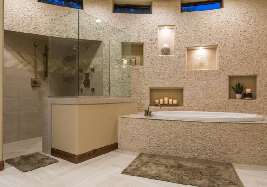 A spacious master bathroom with a tall ceiling. It offers a drop-in tub along with a walk-in shower area.