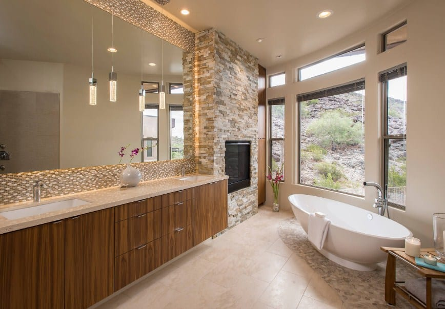 A southwestern primary bathroom featuring a freestanding tub near the windows along with a fireplace and two sinks lighted by pendant lights.