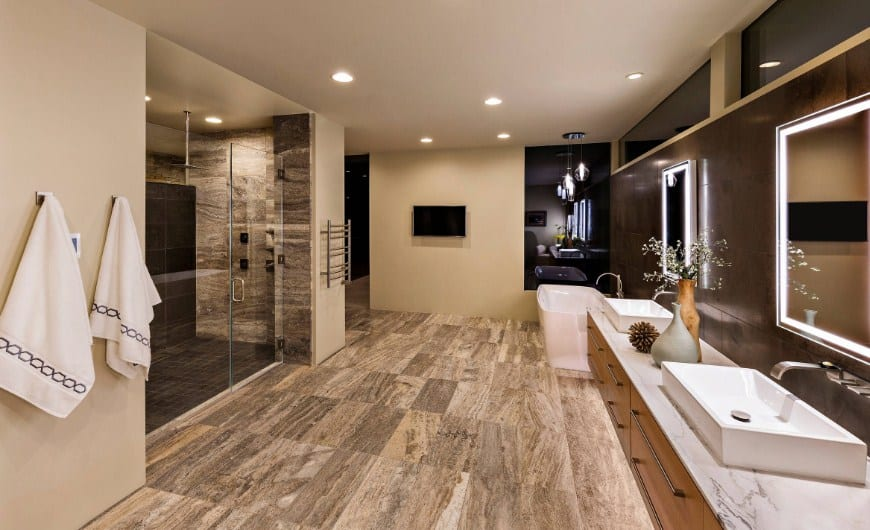 Large primary bathroom featuring stylish flooring and walls. It offers a floating vanity with two vessel sinks along with a freestanding tub and a walk-in shower room.