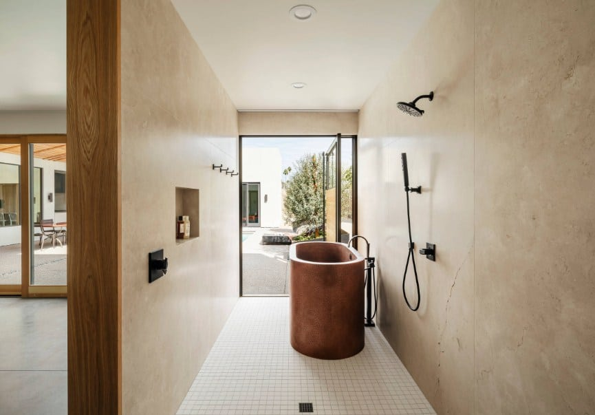 This primary bathroom has a narrow space and offers a freestanding deep soaking tub and an open shower.