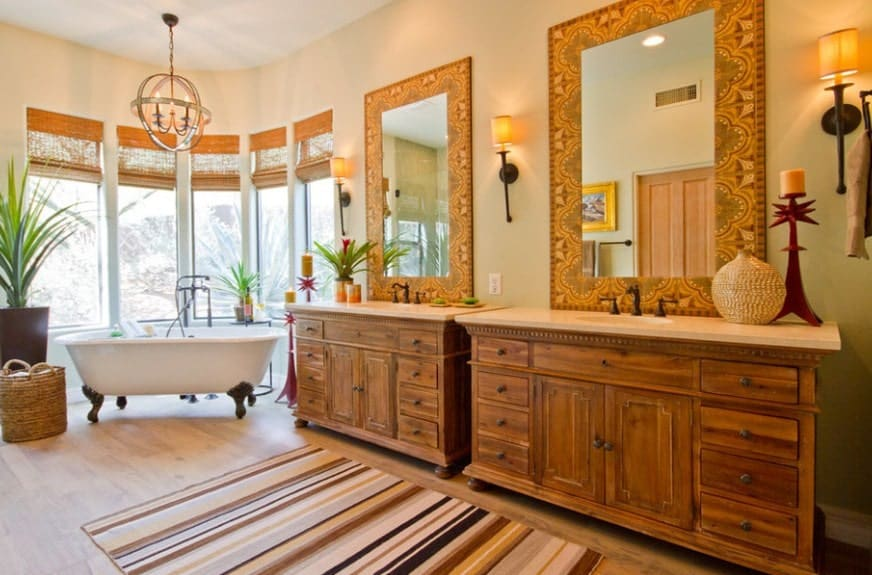 A large primary bathroom with hardwood flooring and beige walls. The room offers two sink counters lighted by wall lights. The freestanding tub is lighted by a gorgeous ceiling light.