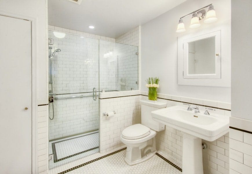 Bright primary bathroom with white tiles flooring and walls. The room offers a walk-in shower and a pedestal sink lighted by a gorgeous wall light.