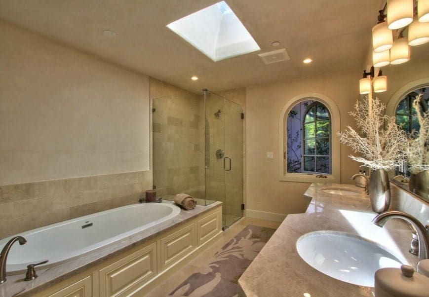 This master bathroom offers a skylight. It also has a drop-in tub, a walk-in shower and a single sink counter with two sinks.