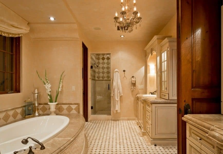 Spacious southwestern style master bathroom featuring beige walls and tiles flooring. The room is lighted by a glamorous chandelier. It offers a drop-in tub and a walk-in shower room.