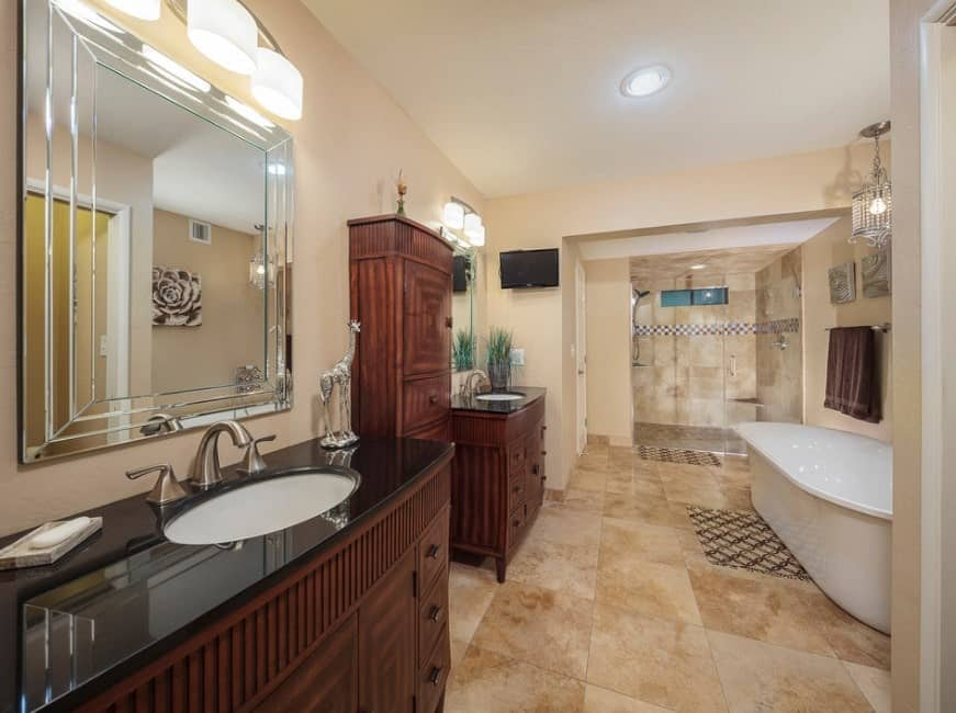 Large master bathroom featuring two sink counters lighted by wall lights along with a freestanding tub and a walk-in shower area.