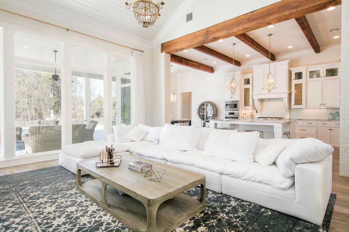 Bright and airy living interior with beam ceilings, white ceiling and walls, and hardwood flooring.